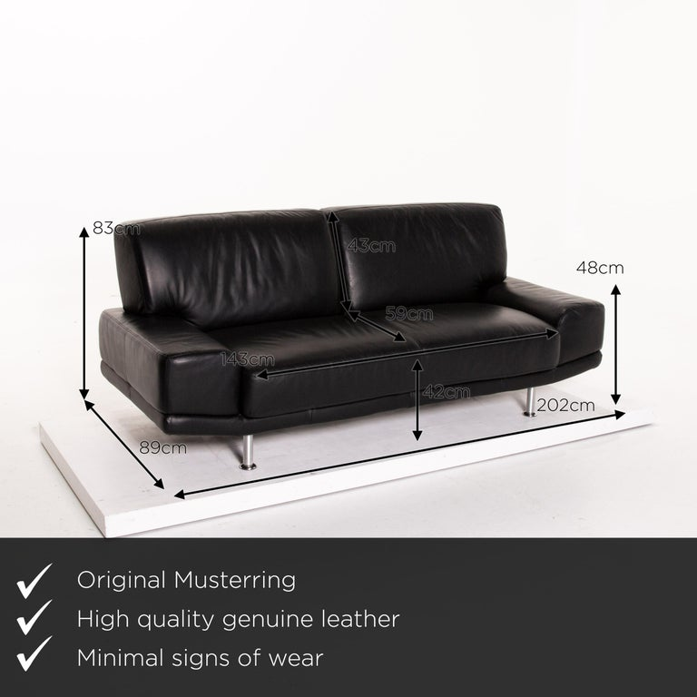 We present to you a Musterring leather sofa black two-seat couch.      Product measurements in centimeters:     Depth 89  Width 202  Height 83  Seat height 42  Rest height 48  Seat depth 59 Seat width 143  Back height 43.