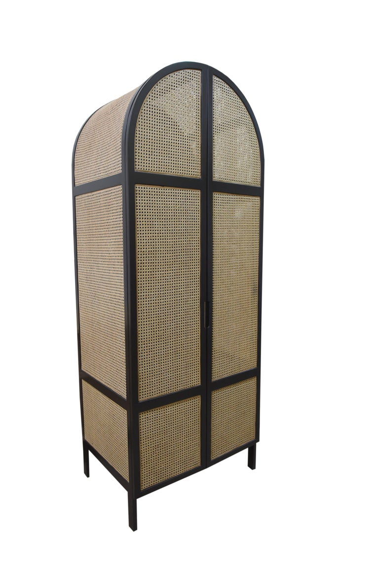Mystery is a handcrafted cabinet featuring an oval design in black lacquered frame and natural handwoven cane. The tight, pulled woven cane will never give an idea of what's inside the cabinet, always protecting its mystery.  This piece is also