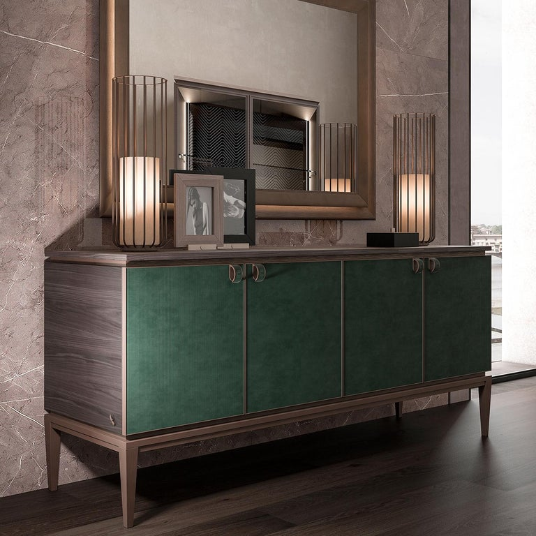 Chic and minimalist yet warm, the Nabuck leather sideboard features cabinet doors lined in supple, resistant nabuck leather. The top surface features a Hungarian herringbone inlaid pattern in natural veneer while the metal base is inspired by