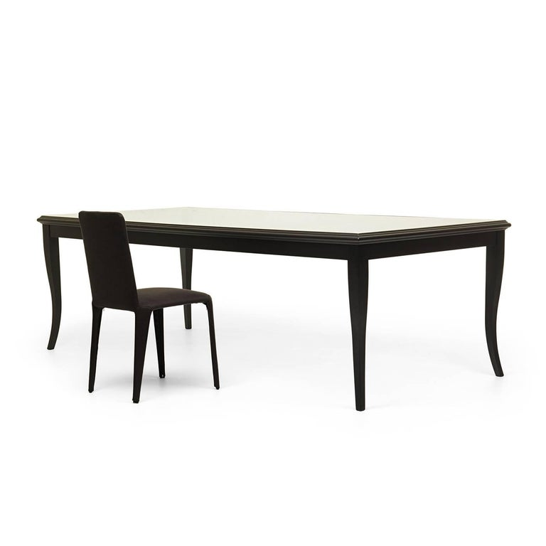 Designed in 2013 by Federico Carandini, this elegant dining table reinterprets the silhouette of an antique table with a contemporary sensibility, creating a light, sophisticated piece that will complement any decor. The tempered glass top showcases