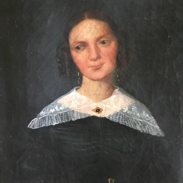 A captivating portrait painting of a beautiful and demure, young woman. 19th century, French, oil on canvas portrait painting in a gilt frame. The painting has stable paint with crazing to the paint surface and some small pinholes. There is an