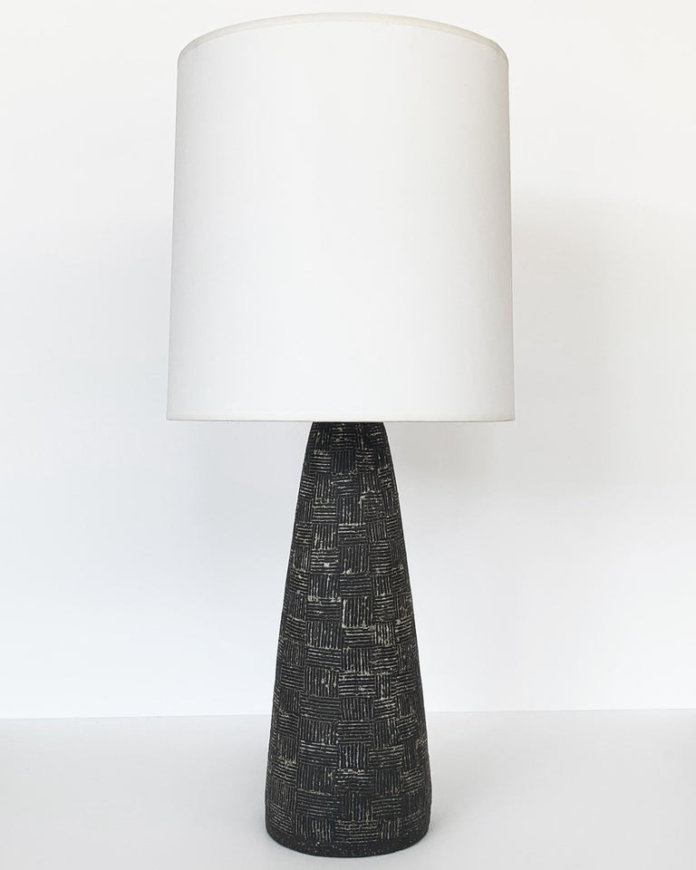 A midcentury ceramic table lamp in a conical form with a textured surface by Nancy Wickham, circa 1950s. Dark grayish brown stoneware with a cross hatched / basket weave design that has been filled in with a white glaze. The carved surface