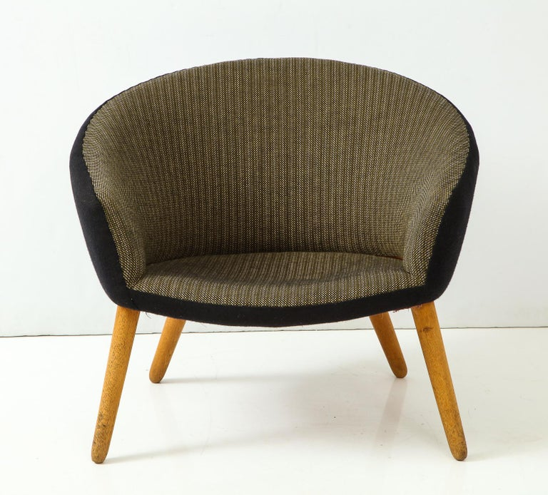 Curved-back lounge chair with splayed oak legs and original two-tone fabric. Designed by Nanna Ditzel and produced in Denmark by A.P. Stolen, circa 1950s. A nice vintage example; the two-tone fabric accentuates the curvilinear shape of the back.