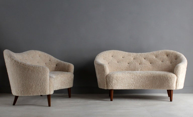 A pair of sofas / love seats attributed to Nanna Ditzel. Soft organic forms are further enhanced by the brand-new, authentic light beige / grey sheepskin upholstery. Mounted on stained beech legs.  Last image illustrates a pair of sofas documented