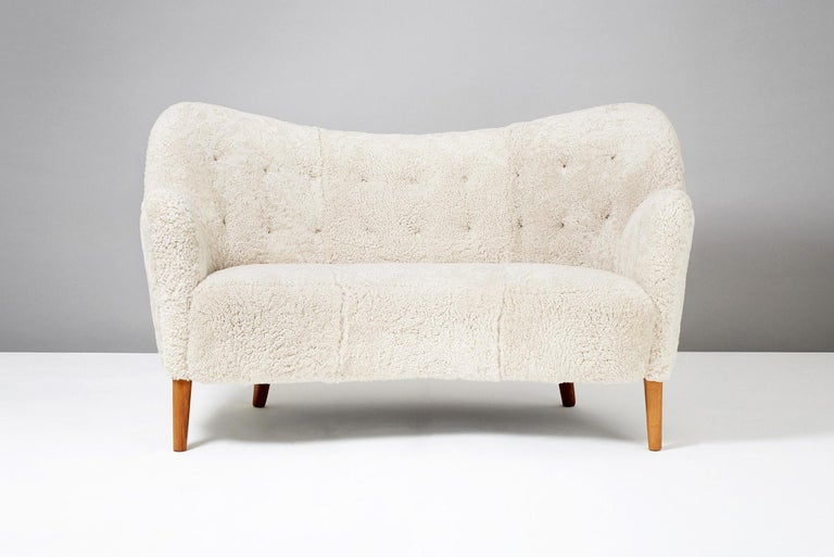 Nanna Ditzel (attributed), Model 185 Sofa, 1952  Rarely seen curved love seat sofa from Danish cabinetmakers Slagelse Mobler. Attributed to Nanna Ditzel. Oiled oak legs and new sheepskin upholstery.
