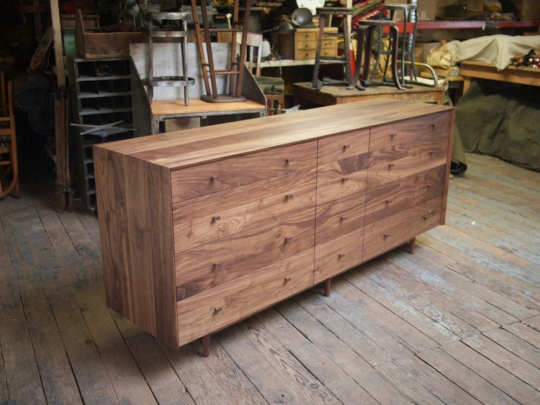 Phloem Studio Naomi Bureau is a solid walnut wood chest of drawers. The hardwood case has a miter from side to top to side. The drawer fronts are grain matched. 12 solid maple wood drawer boxes slide easily with self closing slides. The knobs are