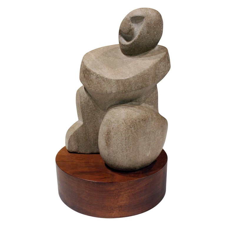 """Hand-carved """"Buddha"""" sculpture in limestone on a wood base by Naomi Feinberg, American 1960s.  Naomi Feinberg was a New York based sculptor who worked primarily in stone. She began sculpting in the 1940s and became affiliated with artist group"""