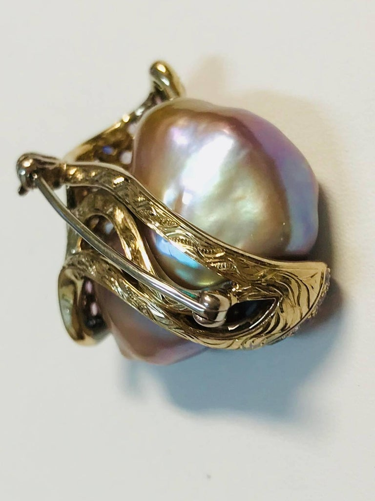 Beautiful Chinese freshwater gray pearl encased in a waved of 18K yellow gold set with approximately 74 multicolored sapphires and diamonds.   Internationally award winning designer Naomi Sarna creates gem carvings and jewels of unusual beauty. She