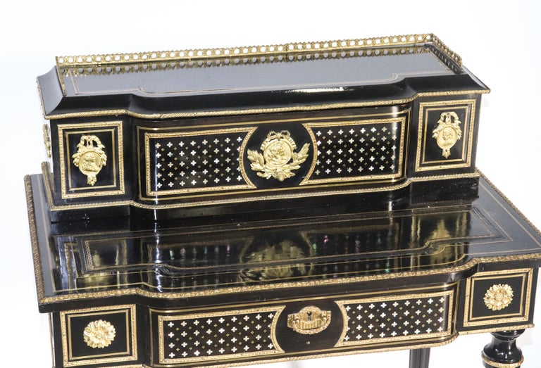 Napoleon III black lacquered Bonheur du jour diminutive writing desk, 20th century, throughout with brass inlay and gilt metal appliques, the desk with tooled leather writing pad, all over four turned and fluted legs. Measures: 36.75