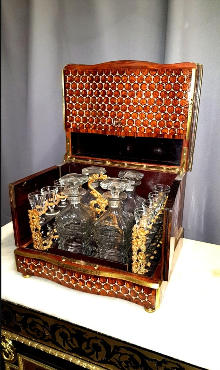 Beautiful liquor cellar cave in marquetry made in fruitwood, geometric patterns on the hood and facade. Glassware composed of 4 carafes and 16 glasses in a mahogany and bronze servant. France, circa 1865. Napoleon III. In a very good general