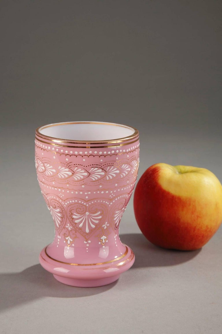 19th century cup crafted in pink opaline glass, embellished with palmettes, small pearls, and foliate motifs in white enamel. Thin bands of gold highlight the enamel as well as the base and rim of the cup. The precise and detailed enamel work