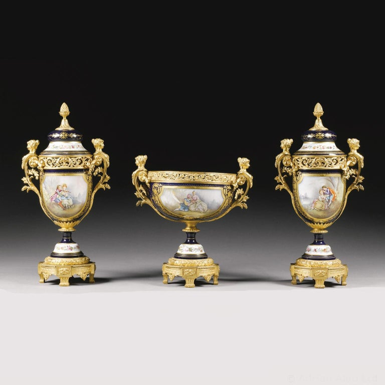 A Napoléon III gilt-bronze mounted Sèvres style garniture set. Comprising a centrepiece and a pair of vases with lids, by 'Robert'.  Each painted on the reverse with bouquets of flowers, to the front with romantic scenes, and mounted with bronze