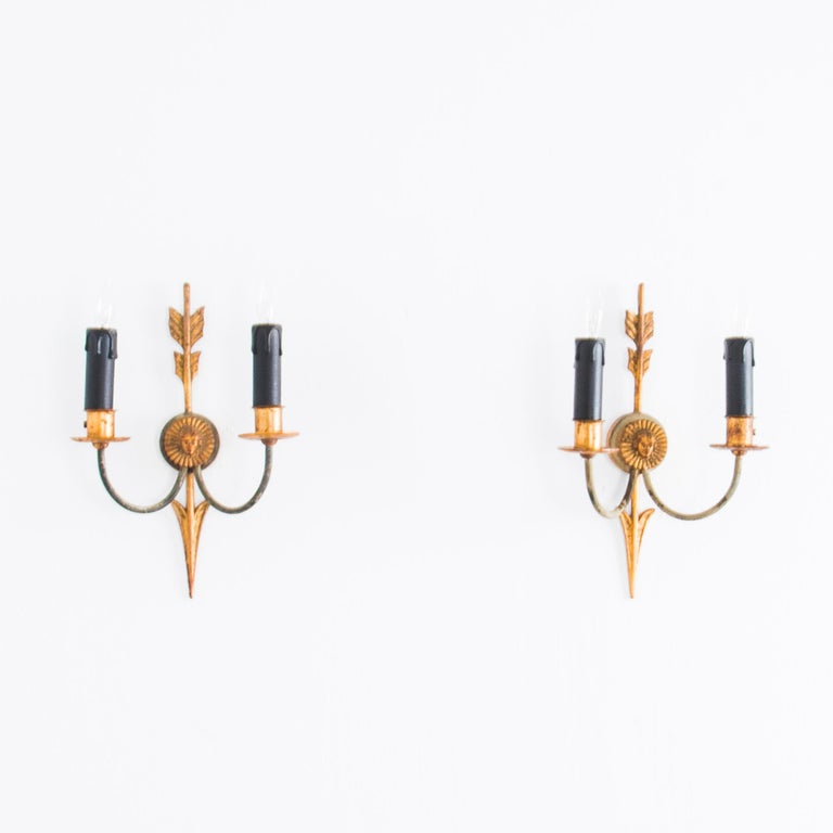 This pair of Second Empire style wall sconces from turn of the century France provide a handsome antique light source. The backplates take the form of a golden arrow piercing a radiant emblem, from which emerge a pair of curved symmetrical arms.
