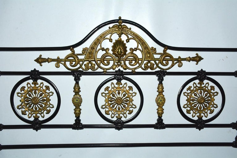 Napoleon III style king bed headboard is constructed of iron and bronze painted black with elaborate solid brass detailing, including filigree rosettes and pediments. The outer posts and legs have a scattering of hand painted pansies and leaves.