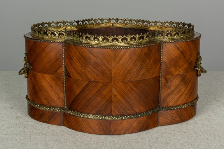 A 19th century French Napoleon III style bronze-mounted jardinière, or planter, made of bookmatched marquetry veneer of mahogany. Decorated with a Sevres porcelain oval medallion, hand painted with a colorful floral bouquet and bright turquoise blue