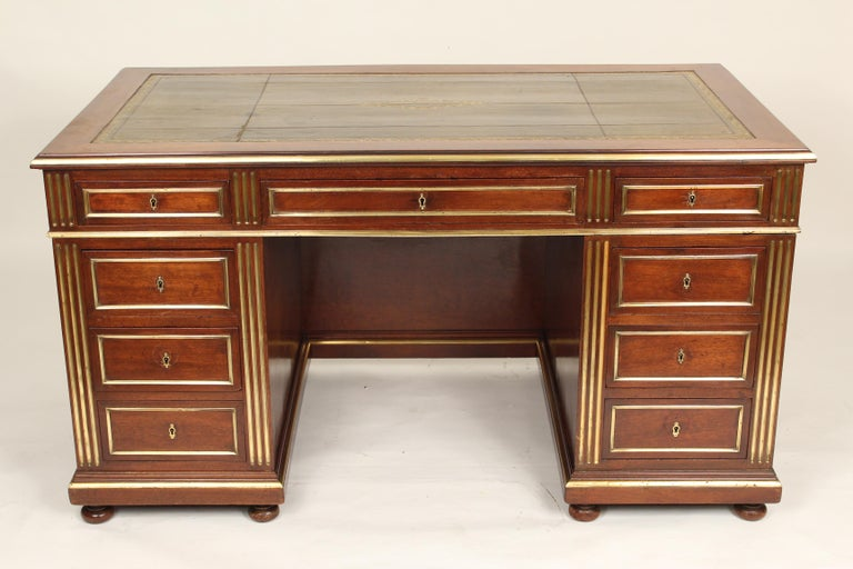 Napoleon III style mahogany double pedestal desk with brass inlay, brass moldings, tooled leather top, modesty board and pull out writing slides on each end, circa 1880.