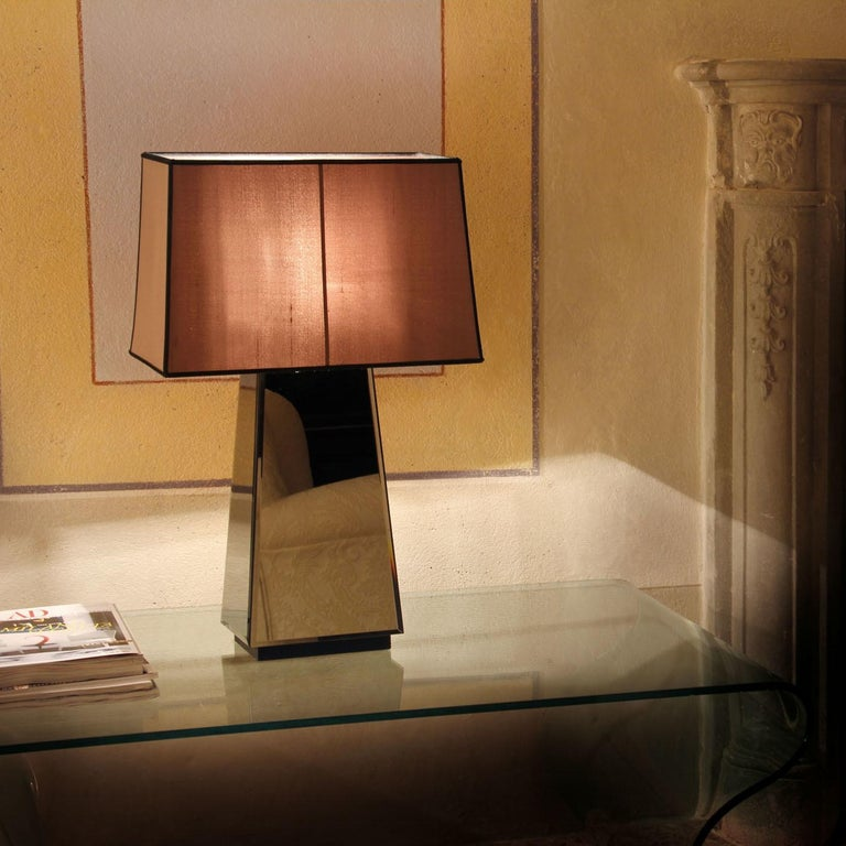 A stunning accessory, with a contemporary design, the Narciso M Table Lamp features a structure covered in smoked bevelled mirror that combines perfectly with the base in wood and lampshade in cotton-linen fabric.\nBulbs: 1 x max 60W E27, 1 x 20W
