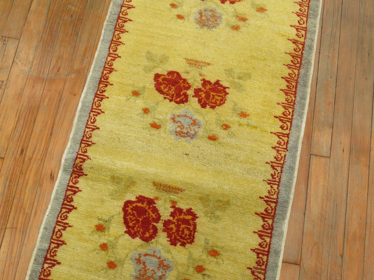 A one of a kind Turkish runner with running flowers on a bright yellow ground.