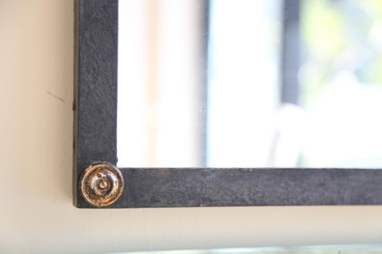 Vintage mirror, having a rectangular looking glass, in frame of black iron, its arched top surmounted by gilt rope detail, the bottom of its frame adorned with buttons at each corner.   Stock ID: D1767.