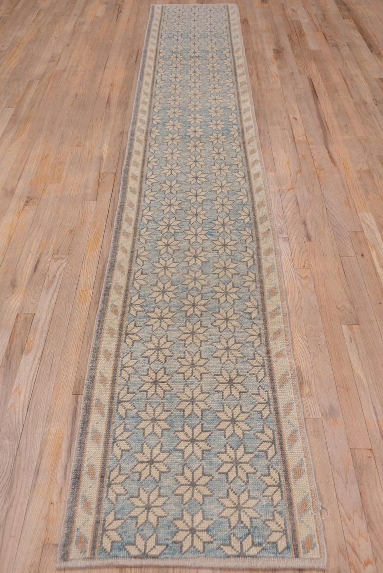 This rustic central Turkish runner displays a watery pale blue field with half drop rows of sand ivory stars and a sand border of rhomboids. The condition is excellent.