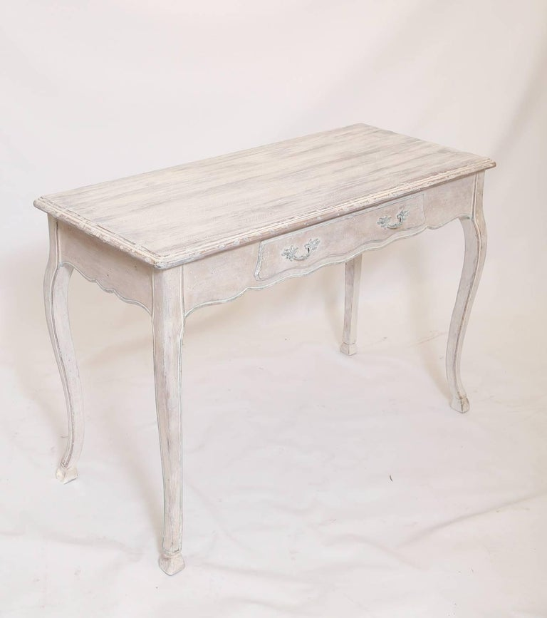 Writing desk or console table, having a painted finish, showing natural wear, its molded, rectangular top on serpentine apron, single frieze drawer with Rococo style pulls, raised on cabriole legs, ending in hoofed feet. 