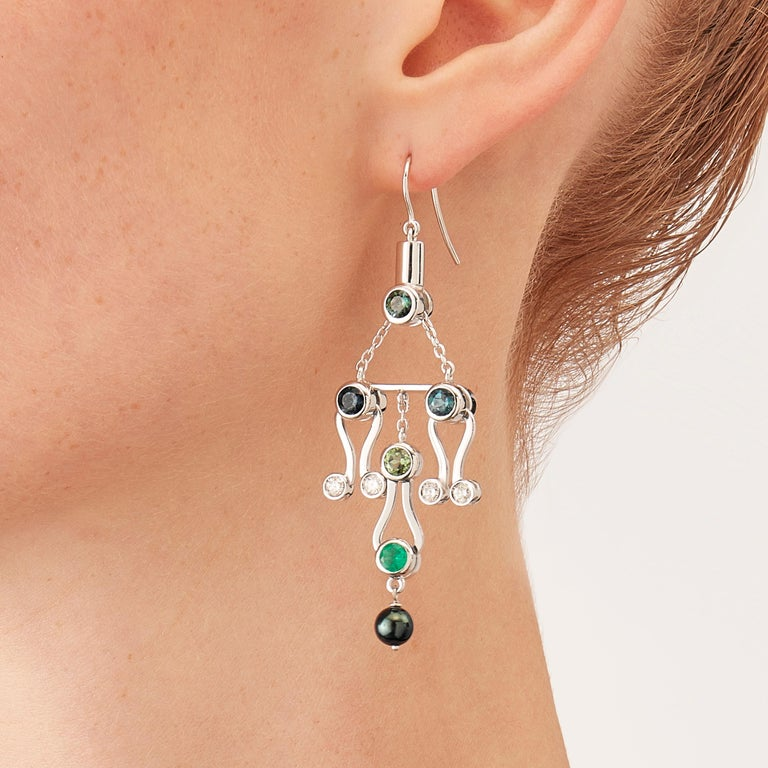 Micro Rock earrings in 18 karat white gold are devised as a game, a construction or a sophisticated aerial mobile. Shapes attached to gold rings dangle lightly on the ear, their geometry pierced by diamonds (0,2 carats), emerald, tourmaline,