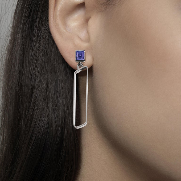 Made by hand in Nathalie Jean's Milan atelier in limited edition, the Saphir Infini drop dangle earrings are composed of polished sterling silver ribbon shapes with rounded edges and square cut iolite. The angular configurations of the sapphire's