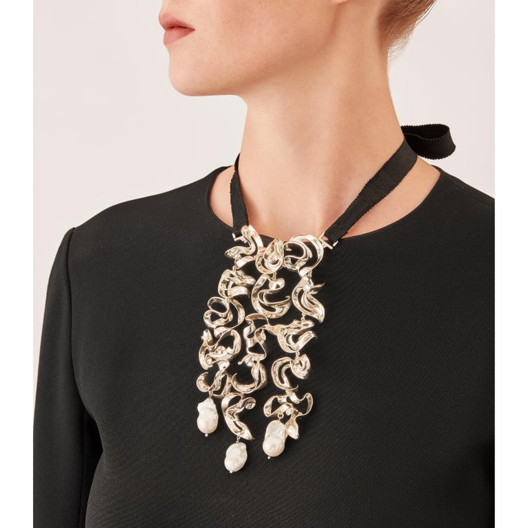 With their delicate, curved, free-form surfaces, the little sculpture elements of this contemporary necklace fold and unfold with harmony and grace like shell fragments or metalized leaves. Linked to each other to form a sterling silver ivy, these
