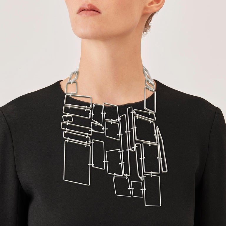 Made by hand in Nathalie Jean's Milan atelier in limited edition, the Saphir Infini Pectoral contemporary drop necklace is composed of matt sterling silver ribbon shapes with rounded edges. Clever hidden links allow the pieces to drape nicely around