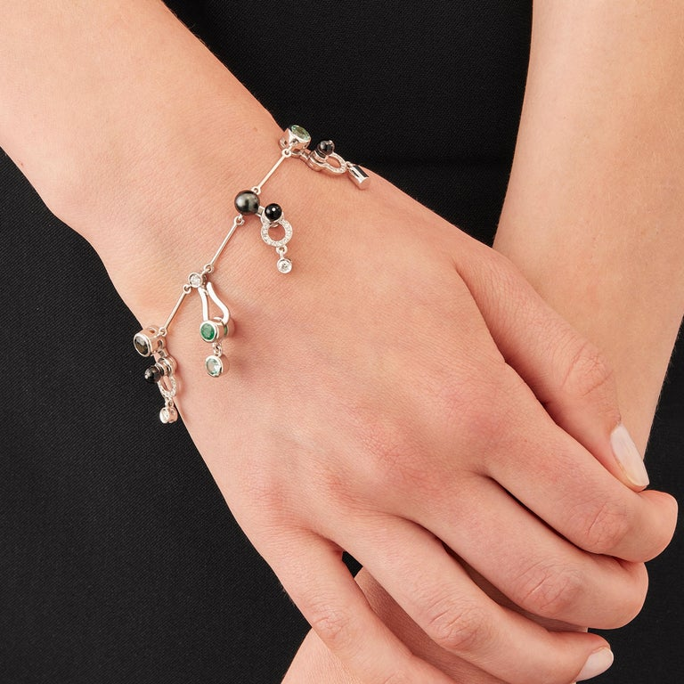 Micro Rock Charm Bracelet is devised as a game, a construction or a sophisticated aerial mobile. Shapes attached to gold rings dangle lightly on the hand, their geometry pierced by diamond, emerald, green tourmaline, indicolite, black pearl and onyx