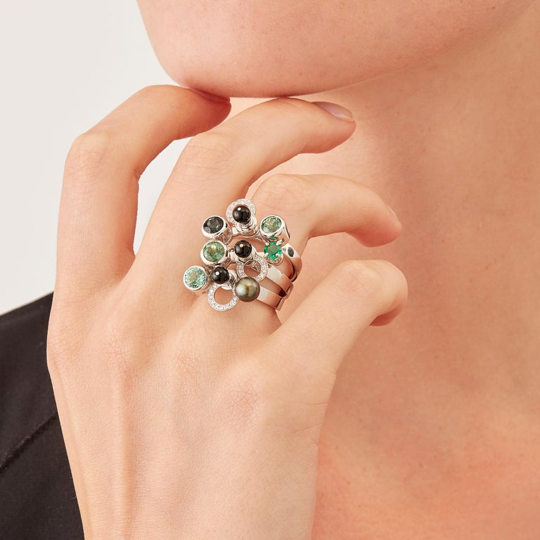 Micro Rock Rings are devised as a game, a construction or a sophisticated aerial mobile. Shapes attached to gold rings dangle lightly on the hand, their geometry pierced by diamond (0,165 carat), green tourmaline, indicolite, emerald, black pearl