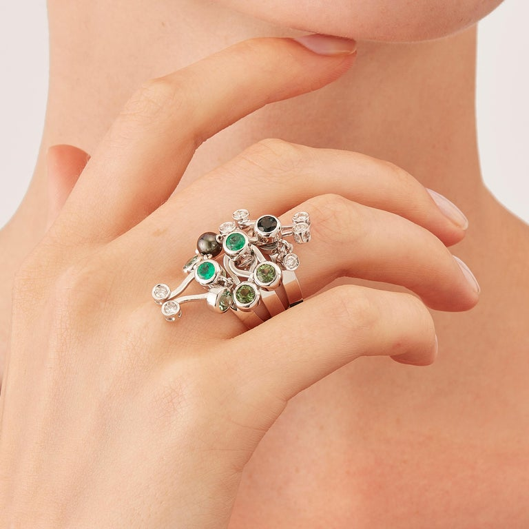 Micro Rock Bis three stack rings are devised as a game, a construction or a sophisticated aerial mobile. Shapes attached to gold rings dangle lightly on the hand, their geometry pierced by diamond (carat total weight 0,35), green tourmaline,