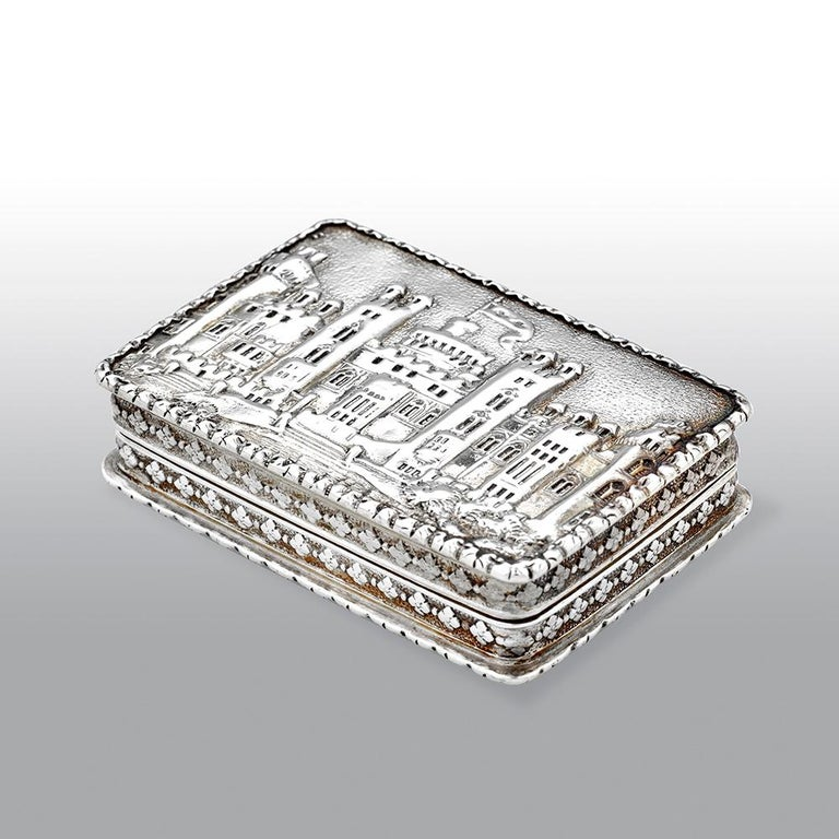 A fine quality silver gilt castle-top vinaigrette of rectangular form with raised foliate borders and sides, the base with engine turned decoration and a rectangular cartouche, the lid with a chased and engraved view in high relief depicting Windsor