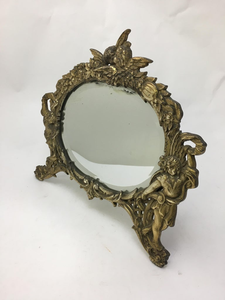 Gilded cast iron standing mirror decorated with floral scroll and putti motif. Oval bevel glass mirror. Fully signed on reverse, NB&IW, 2000, circa 1910.   Measures: 6