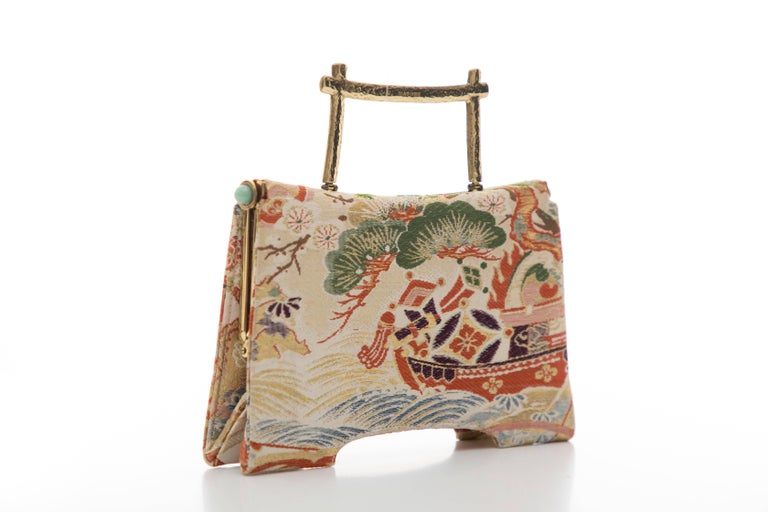 Natori jacquard top handle bag with gold-tone hardware, single flat top handle, jade embellishments at side, black  woven lining, dual pockets at interior wall; one with zip closure and push-lock closure at top.  Handle Drop: 2, Height 5, Width