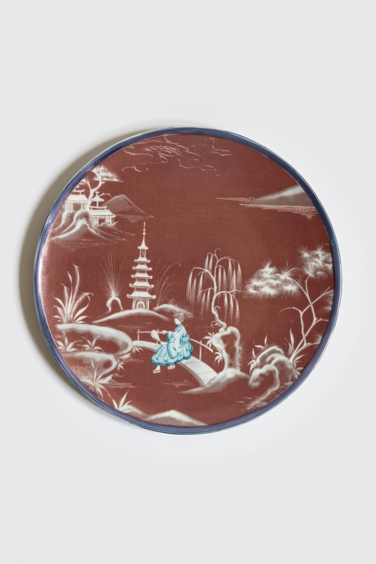 Bordeaux and blue are the primary colors of this Japan inspired collection of plates, where ancient Japanese scenes take place on the rivers of a fairy lake.