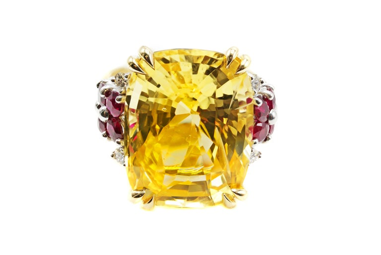 A gorgeous cushion cut deep-lemon-colored natural yellow sapphire, weighing 16,68 carats, is set withing a contemporary beautifully designed ring mount by Rive Gauche Jewelry. The high polished 18 karat yellow gold mounting has the gemstone securely