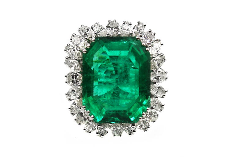 Magnificent Natural Colombian Emerald, weighing approximately 25 carats, set in a custom hand crafted 18 karat white gold mounting. Triple prong set at each corner secure this center gem and it is surrounded by 25 marquise cut and pear shape bright,