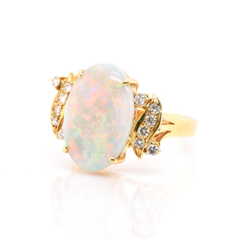 A beautiful Cocktail Ring featuring a Natural Australian White Opal and 0.25 Carats of Diamond Accents set in 18K Yellow Gold. Opals are known for exhibiting flashes of rainbow colors known as