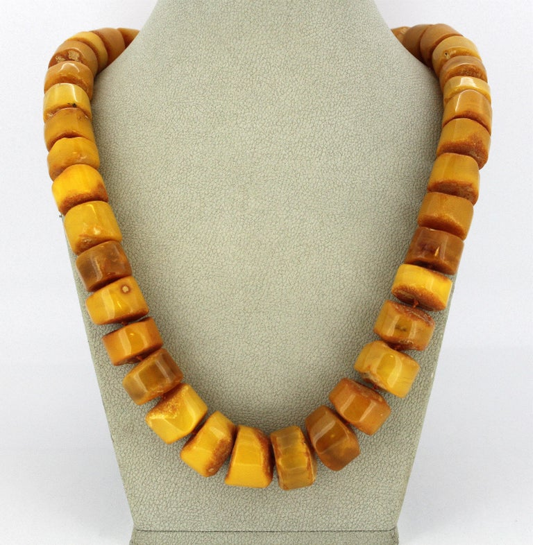 Natural Baltic amber necklace in the form of half polished tablets, with sterling silver clasp. Hallmarked 925. Circa 1950's  Dimensions - Length : 52 cm Width : 1.9 cm Weight : 80 grams  Amber -  Treatment : Natural  Condition: Pre-owned, general