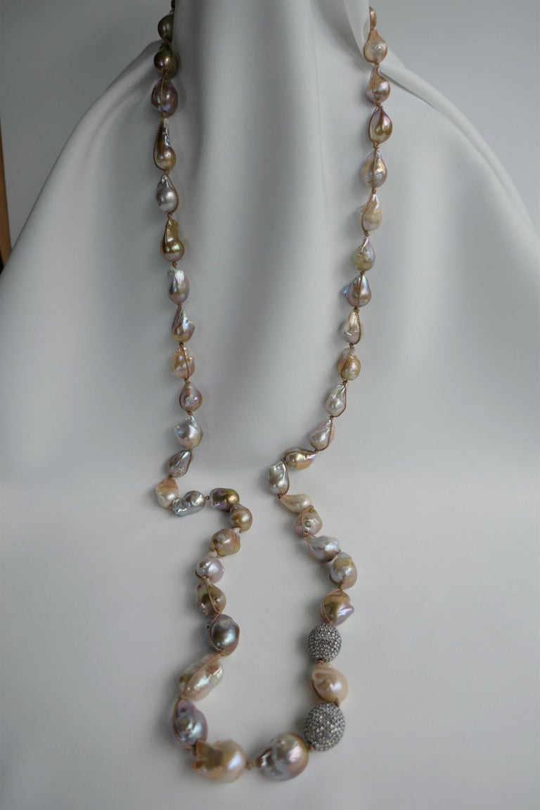 This is a long natural baroque cultured pearl necklace. The natural baroque pearls are 12mm-15mm. The baroque cultured pearl tones are beautiful. The necklace in individually knotted on silk cord and the cord is wrapped on the outside of the baroque