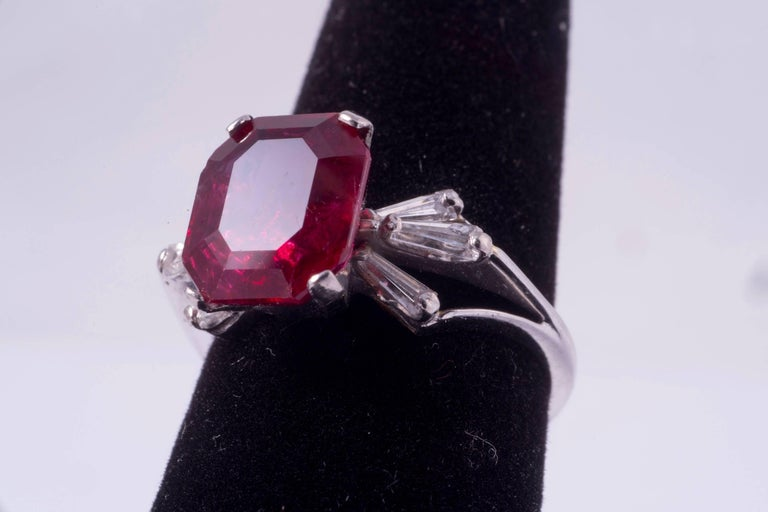 Beautiful natural, rectangular cut Burma ruby ring. The ruby weighs 4.21ct and measures 10.43 x 8.63 x 4.55mm.  The ruby was graded by the AGL, Report number CS 42640. The mounting is platinum with three taper baguettes on either side. Ring size