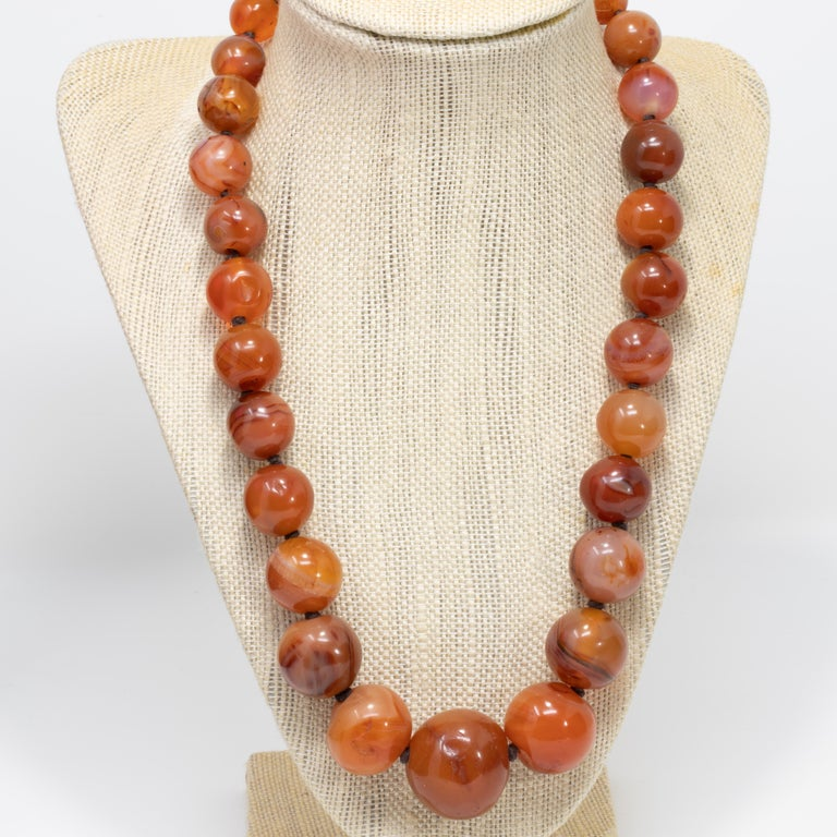 An extravagant carnelian graduated bead necklace on a dark brown knotted string. Features genuine carnelian beads ranging from 9.5mm to 25.5mm in diameter, fastened with a 16mm long 585 (14 karat) yellow gold clasp. A rich, dark orange, translucent