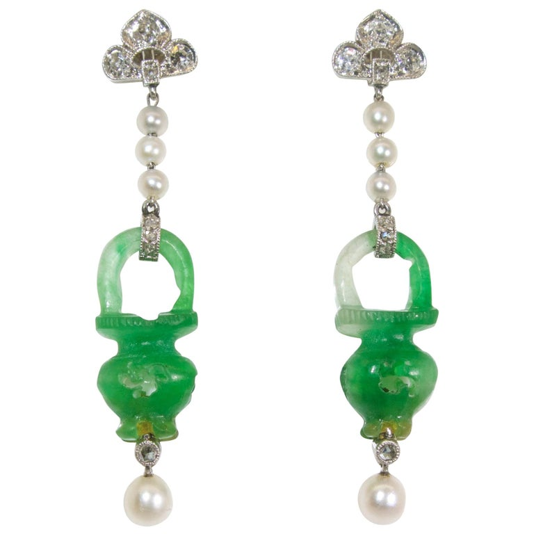 Earrings suspending natural jadeite jade (accompanied by a certificate) carved in an urn motif in round.  The delicate earrings are platinum with eight natural pearls and 22 small old cut and rose cut diamonds.  These delicate earrings, in fine