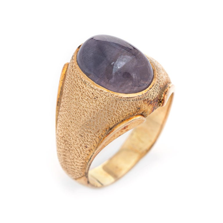 Stylish vintage natural Ceylon no heat star sapphire ring (circa 1960s to 1970s) crafted in 14 karat yellow gold.   Cabochon cut natural Star Sapphire, approx. 9 carats (12.8 x 8.3 x 7.5mm), light purplish color, lightly included, good polish,