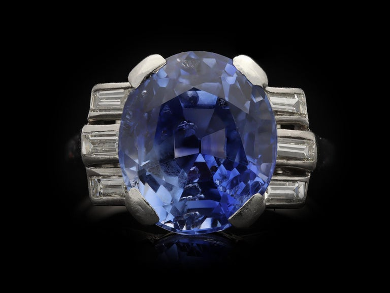 Ceylon sapphire and diamond ring. Centrally set with an oval old cut natural unenhanced Ceylon sapphire in an open back claw setting with an approximate weight of 9.30 carats, flanked by six horizontally set rectangular baguette cut diamonds in open