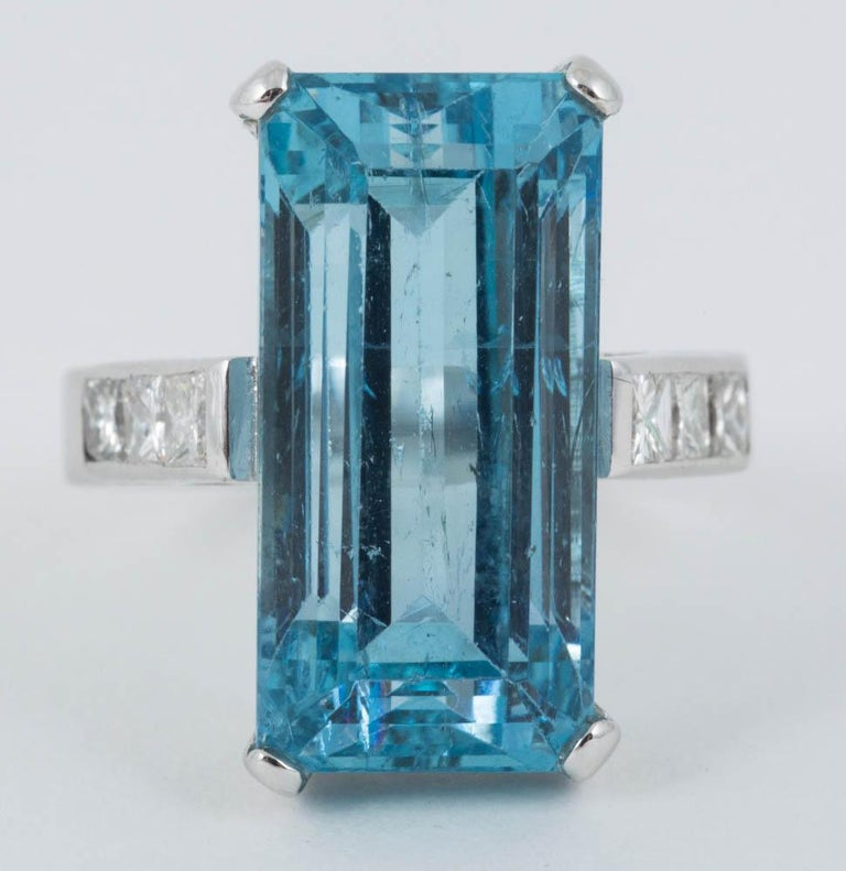 size A Natural coloured Aquamarine ring of Emerald cut measuring 18mm in length and 9mm wide mounted in 18ct white gold,with three,square cut diamonds in each shoulder c,1980 size N and a half