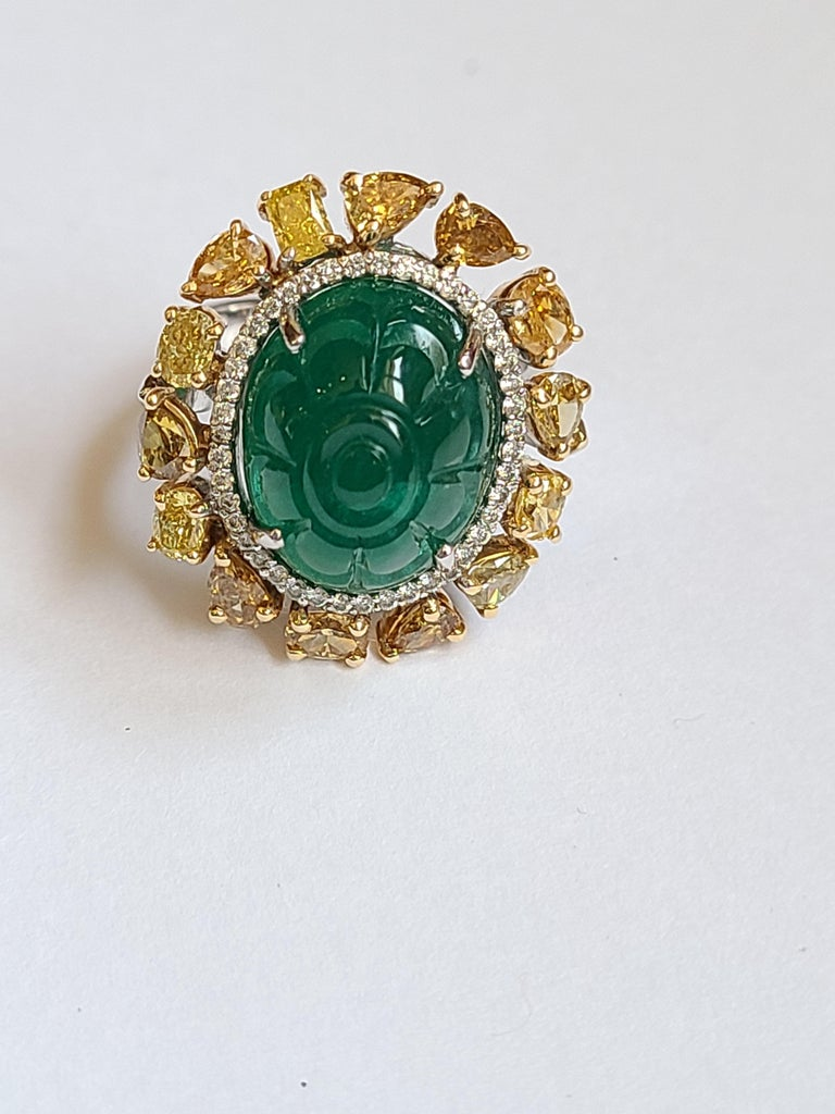 A beautifully carved natural emerald ring set in 18k gold with natural fancy color diamond. The emerald is natural and weight is 10.20 carats , diamond weight is 2.22 carats.  ring dimension in cm 2 x 1.8 x 3 (LXWXH) . US size 6 1/2.