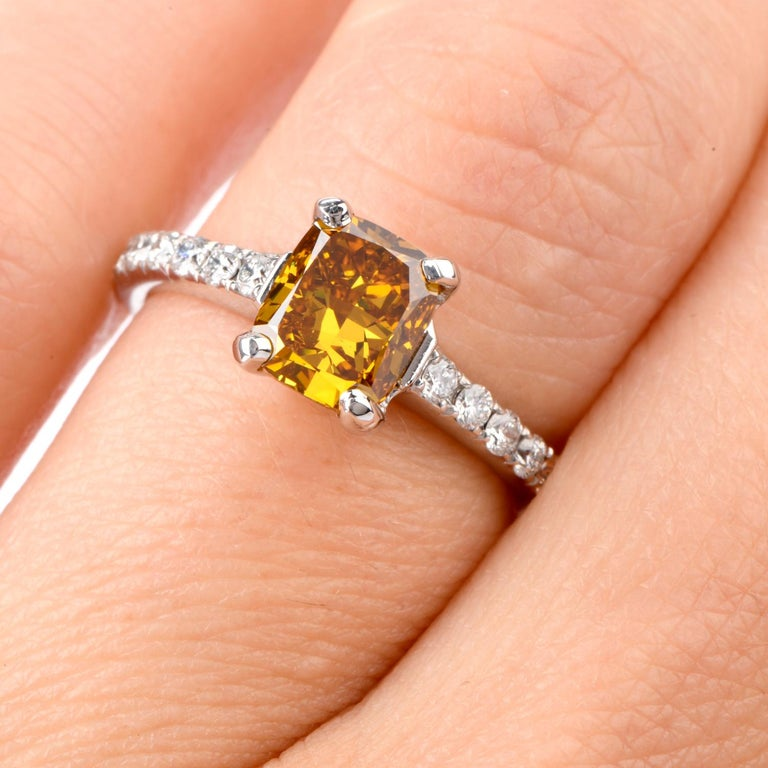 Not an Engagment Ring like all others!  This stunning ring features a GIA Certified 1.60 carat cushion shaped natural Fancy Deep Orage-Yellow SI1 clarity Diamond in the center and bright white diamonds on either side and down the shoulders.  These