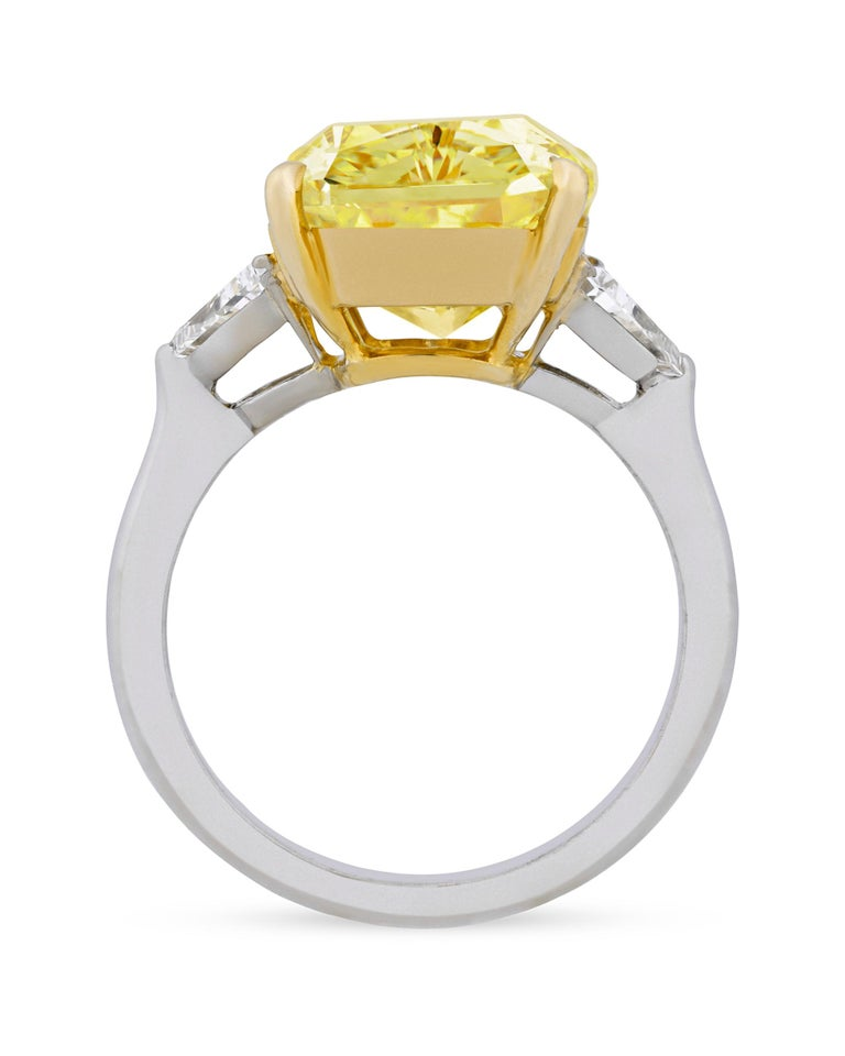 An exceptionally rare and astonishing 8.06-carat fancy intense yellow diamond reflects the radiance of pure sunshine in this incredible ring. Two dazzling white accent diamonds weighing 0.50 carats each flank this breathtaking gemstone, joined
